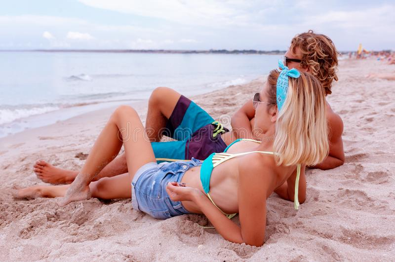 Portrait of young couple in love at beach and enjoying time being together. Young couple having fun on a sandy coast. Portrait of young couple in love at beach royalty free stock image