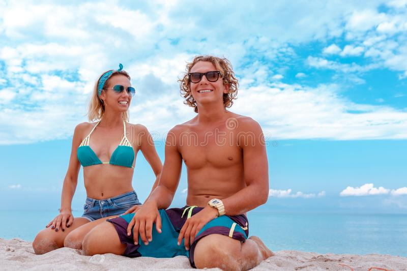 Portrait of young couple in love at beach and enjoying time being together. Young couple having fun on a sandy coast. Portrait of young couple in love at beach stock photo