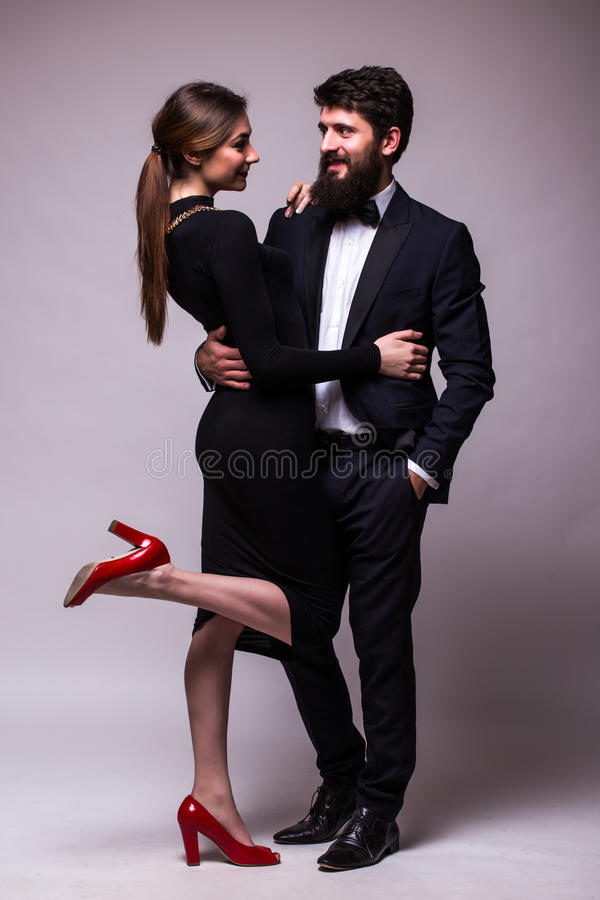 Portrait of young couple in love posing dressed in classic clothes on grey backround. Man with beard in Suit, Woman in black Dress stock photos