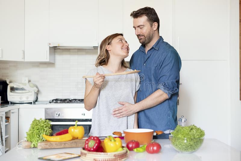 Happy couple in home kitchen cooking together vegetables. Portrait of young couple in love preparing food stock photography