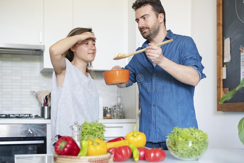 Portrait of young couple in love preparing food. Happy couple in home kitchen cooking together vegetables royalty free stock image