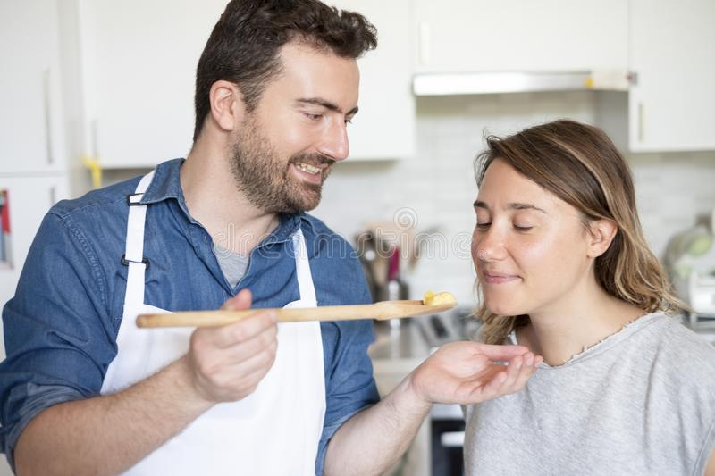 Portrait of young couple in love preparing food. Happy couple in home kitchen cooking together vegetables stock images
