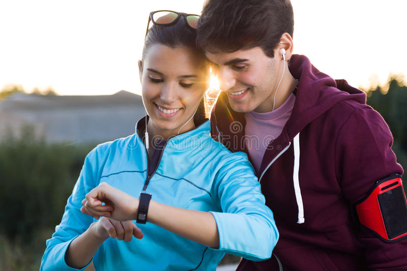 Portrait of young couple using they smartwatch after running. Outdoor portrait of young couple using they smartwatch after running royalty free stock photo