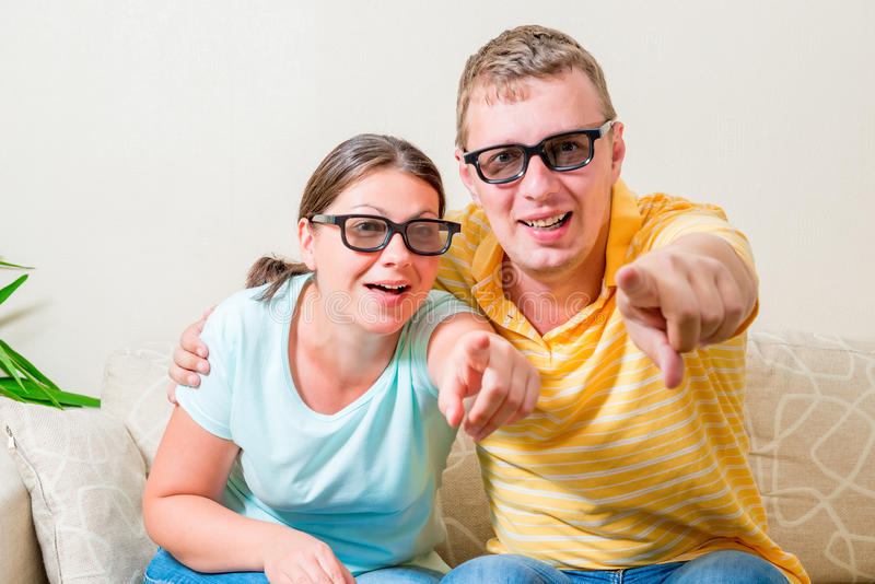 Portrait of young couples looking TV in 3D glasses stock photos