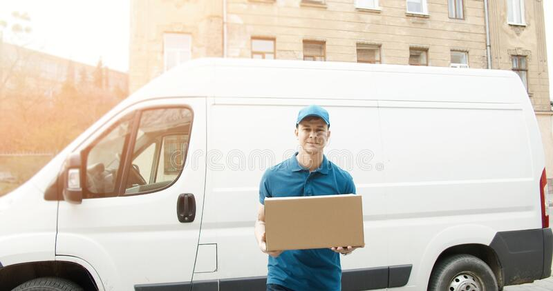 Portrait of young courier in mask standing near delivery car and holding carton box royalty free stock photos