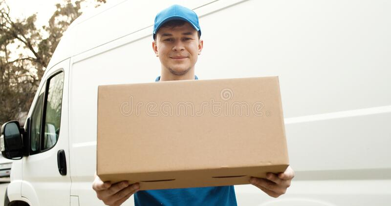 Portrait of young courier in mask standing near delivery car and holding carton box stock images