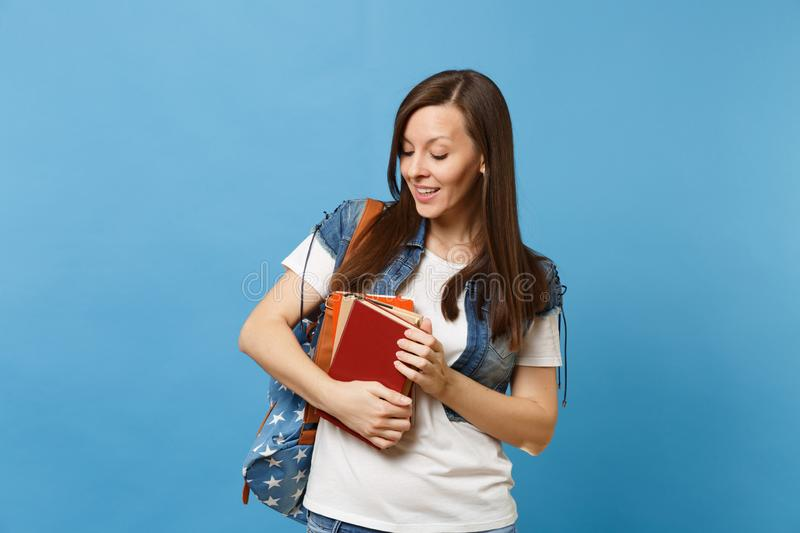 Portrait of young curious nice woman student with backpack holding and looking down on school books ready to learning royalty free stock photography