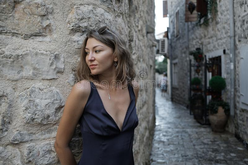 Portrait of Young curly blonde woman in long dress and sunglasses walks around the old town in Budva, Montenegro. Slow motion royalty free stock photos
