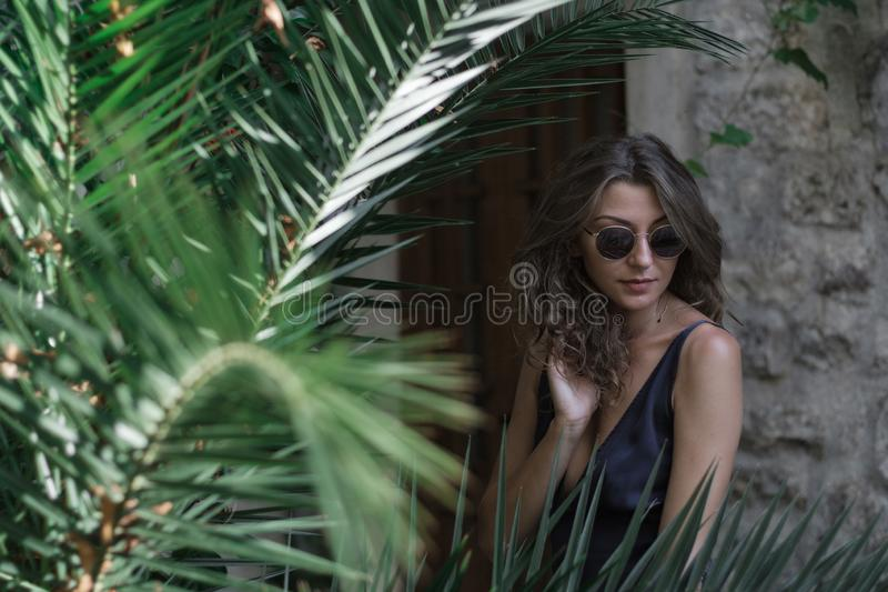 Portrait of Young curly blonde woman in long dress and sunglasses walks around the old town in Budva, Montenegro. Slow motion royalty free stock images
