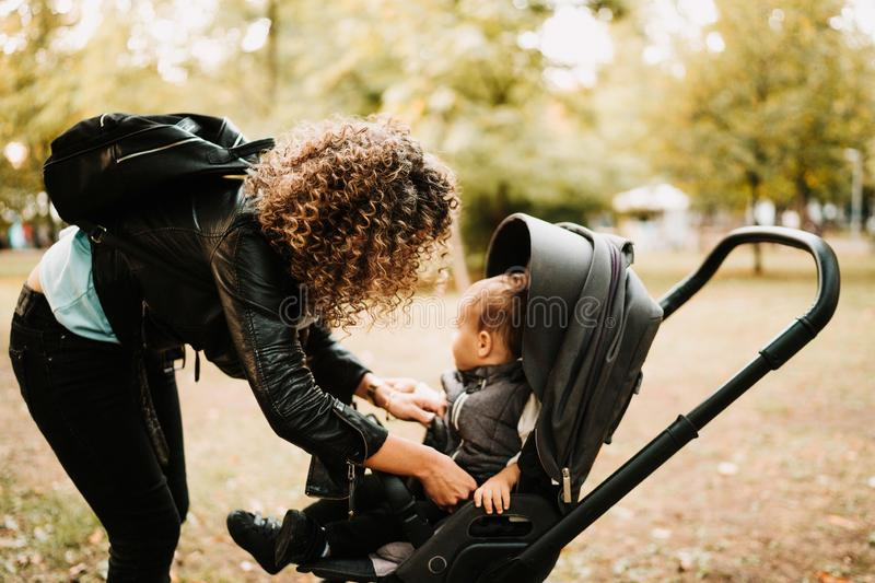 Portrait of young curly haired mother talking with baby in stroller stock photo