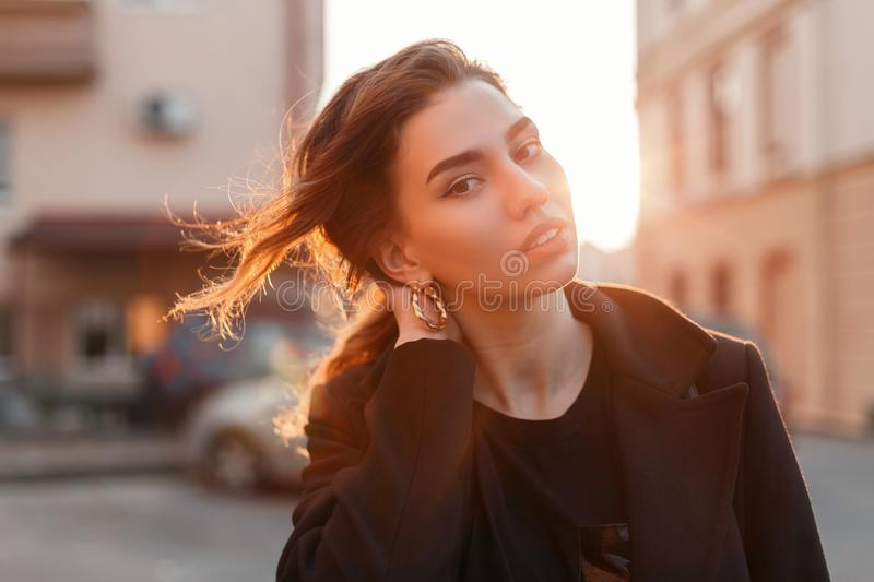 Portrait of a young cute attractive woman with a stylish hairstyle with beautiful eyes with sexy lips in fashionable black clothes. On a background of bright stock image