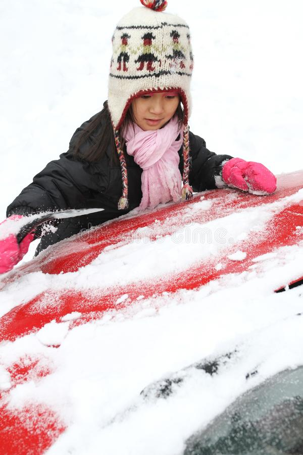 Portrait of a young cute girl looking at the camera romoving snow from a car stock images