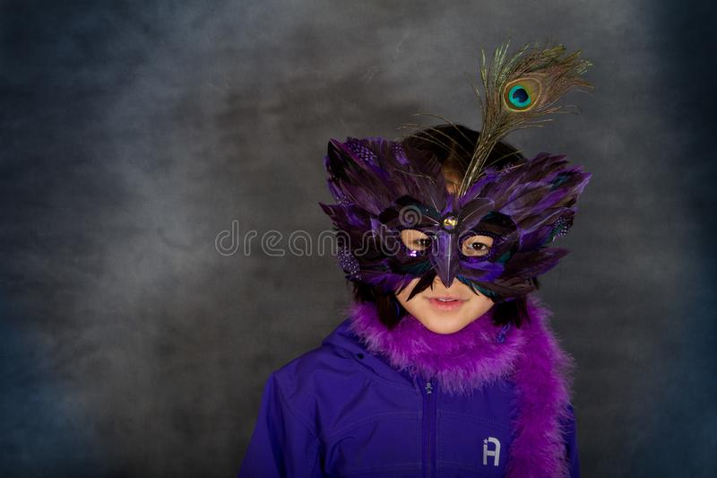 Portrait of a young cute girl with a mask looking at the camera stock photography