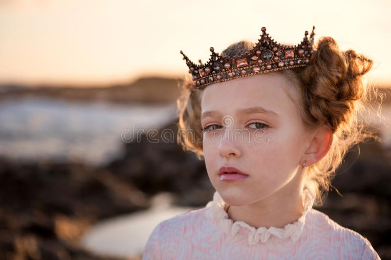 Portrait of a young capricious princess in the rays of the rising sun in the crown. Portrait of a young cute girl in the rays of the rising sun in the crown royalty free stock images