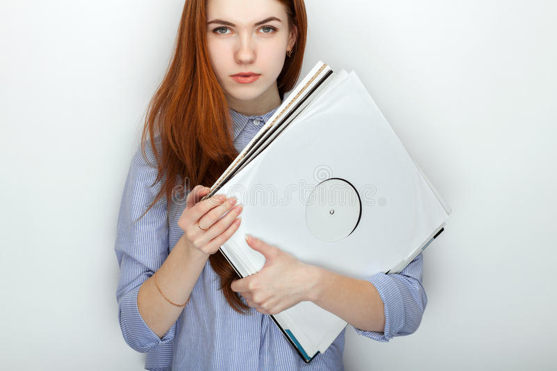 Portrait of young cute redhead woman wearing blue striped shirt smiling with happiness and joy while posing with vinyl records. Against white studio background royalty free stock photography