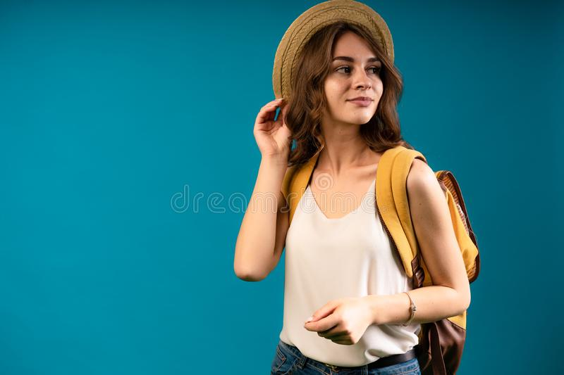 Portrait of a young cute student indoor. White blause. Curvy brown hair. And a straw hat stock images