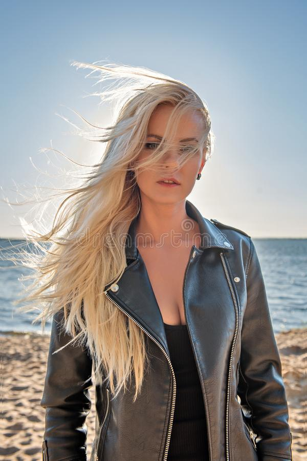 Portrait of a young cutie blond girl in a leather jacket with hair flying from the wind on the beach stock images