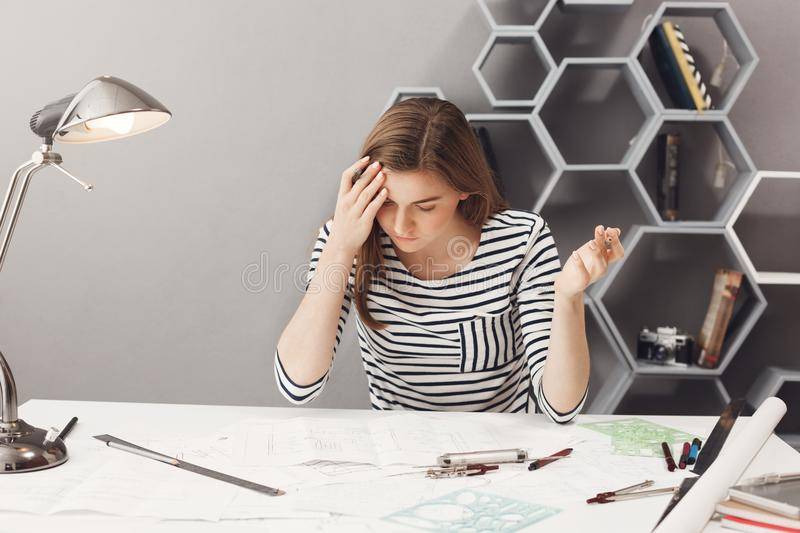 Portrait of young dark-haired handsome female freelance designer in striped casual shirt spreading hands, being. Frustrated, noticing big mistake in financial stock image