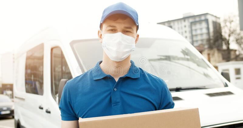 Portrait of young courier in mask standing near delivery car and holding carton box royalty free stock photo