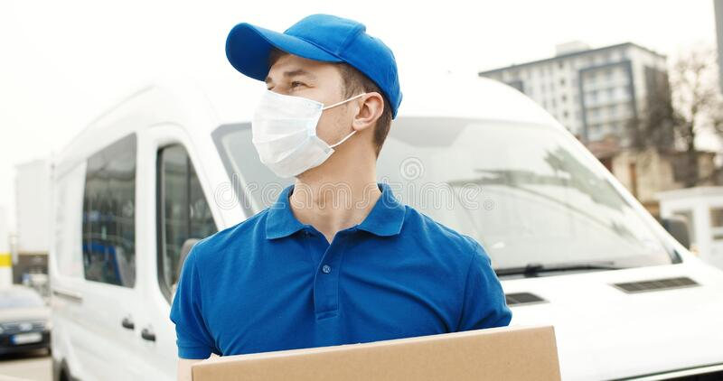 Portrait of young courier in mask standing near delivery car and holding carton box stock photo