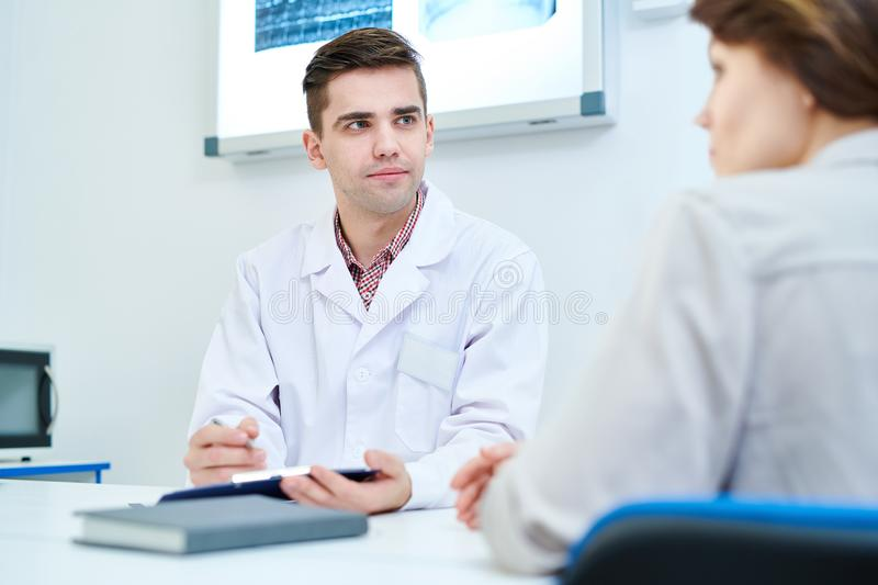 Young Doctor in Office. Portrait of young doctor listening to patients symptoms sitting at desk in office, copy space royalty free stock images