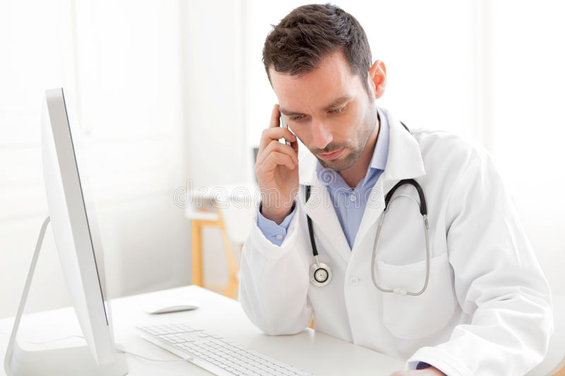 Portrait of a young doctor phoning a patient stock photos