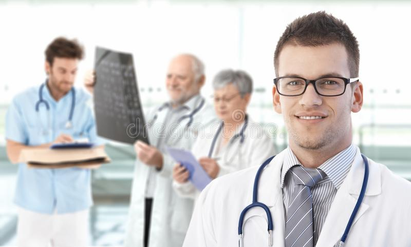 Portrait of young doctor with team in background royalty free stock photography