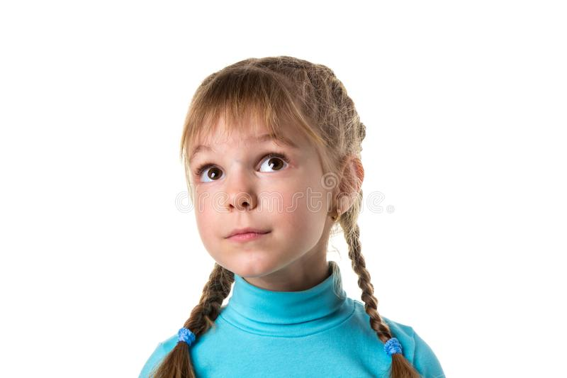 Portrait of a young dreamy naive girl with big eyes, looking up. Girl with two braids, isolated on white landscape royalty free stock photos