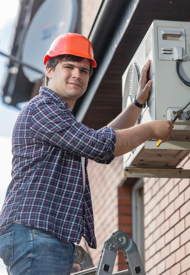 Portrait of young electrician repaiting outer unit of air conditioner royalty free stock photos