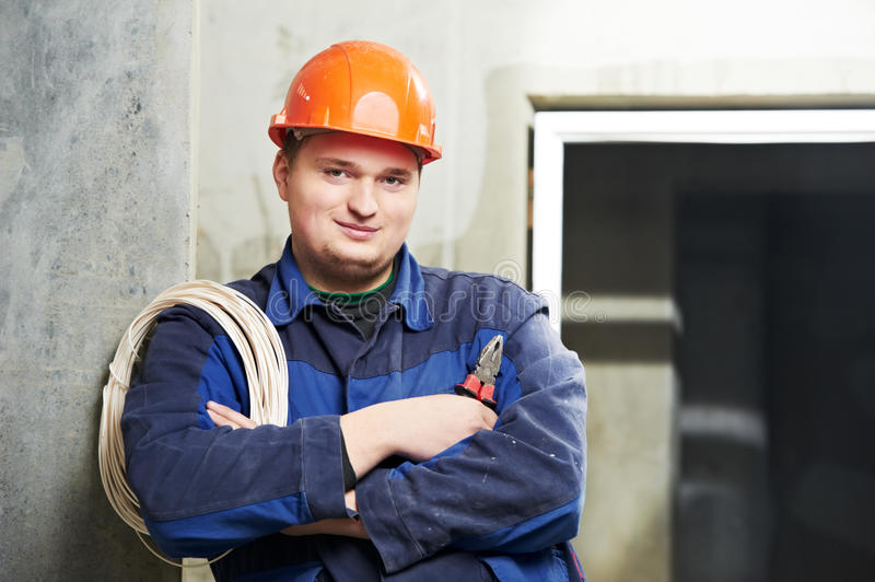Portrait of young Electrician in uniform. One Portrait of young Electrician in uniform with wire cable and pliers stock image