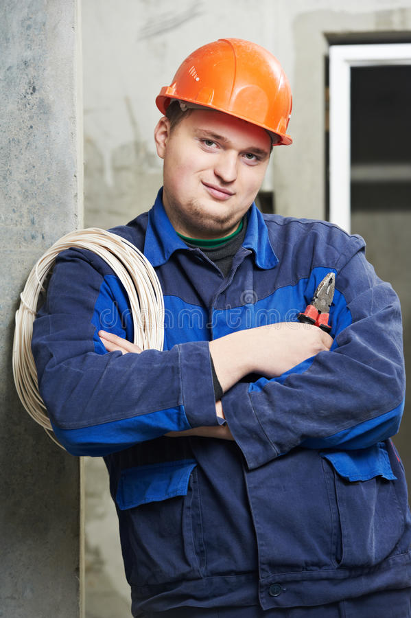 Portrait of young Electrician in uniform. One Portrait of young Electrician in uniform with wire cable and pliers stock photo