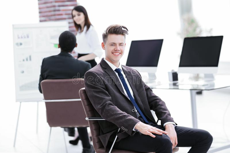 Portrait of young employees sitting near the desktop stock photo