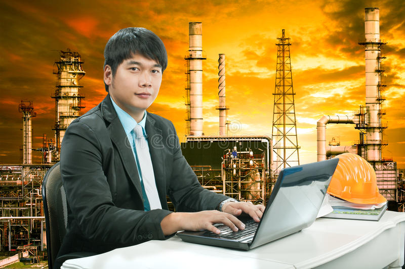 Portrait young engineering man sittin and working on laptop com. Puter against oil refinery industry estate stock photo