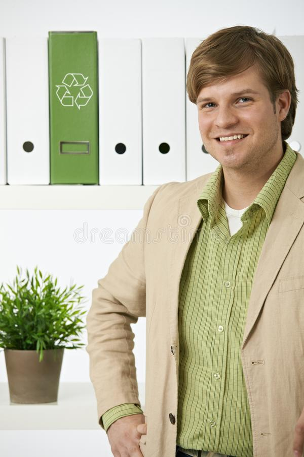 Portrait of young environmentalist man. Posing in front of shelf in office, recycling logo on green folder stock images