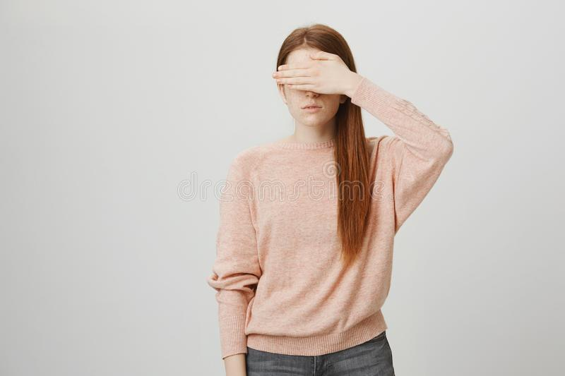 Portrait of young european ginger girl being calm and serious, covering eyes with hand, wearing trendy pullover and. Standing over gray background. Concept of royalty free stock photo