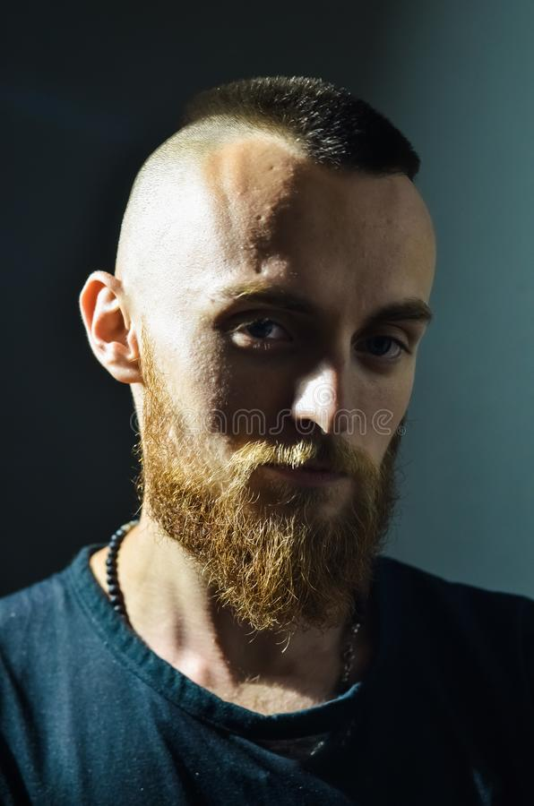 Portrait of young European hipster with fair skin and trendy ginger beard. Fashionable undercut hairstyle and handsome face featur. Es. Mohawk hairstyle stock photography