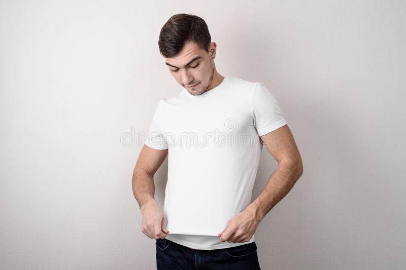 Portrait of a young European man looking at a white empty t-shirt, a place for advertising royalty free stock photos