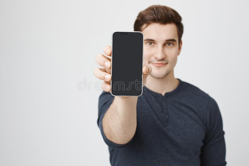 Portrait of young european model advertising new smartphone, showing it to camera, standing over gray background. Shop stock photos