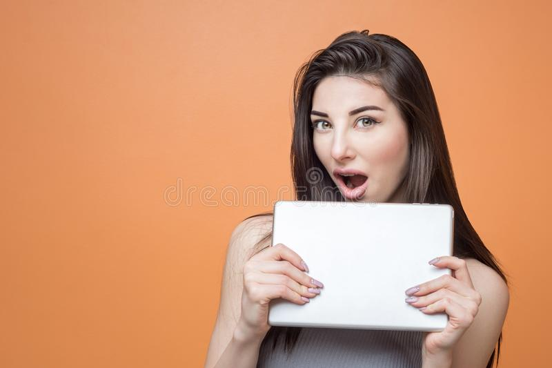 Portrait of a young excited brunette girl with tablet in her hands looking at the camera with open mouth against orange background royalty free stock images