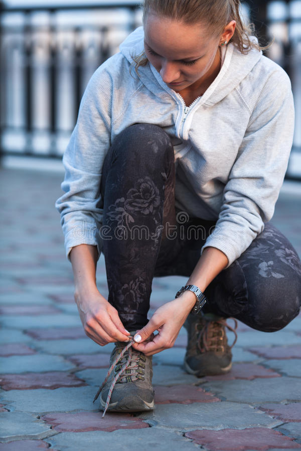 Portrait of a young exercise woman tying her shoelaces royalty free stock image