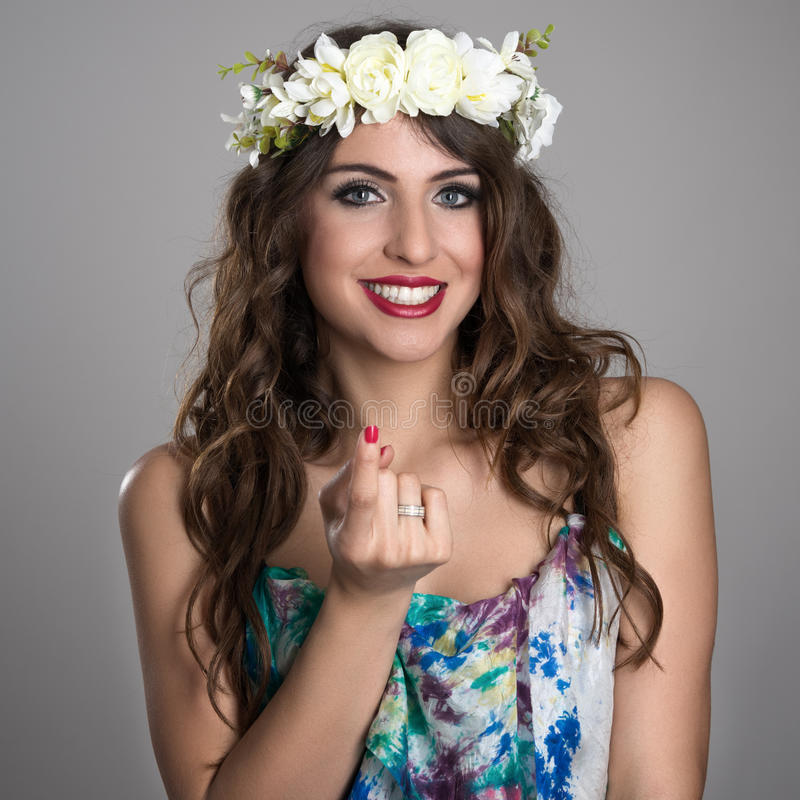 Portrait of young fairy girl with flower wreath smiling with inviting finger gesture royalty free stock photos