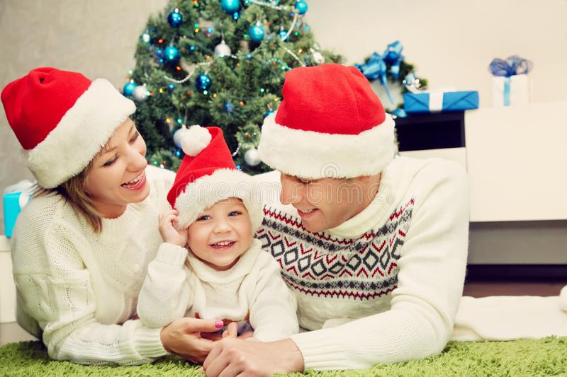 Portrait of a young family. celebration at home. father, mother and child on the background of the Christmas tree. New royalty free stock image