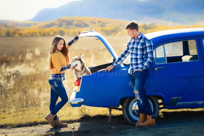 Portrait of a young family with a dog near a convertible. stock images
