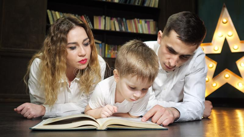 Portrait of young family mom, son and dad are reading a book together. stock photo