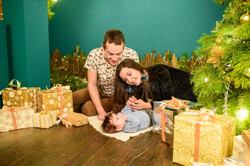 Portrait of a young family near the Christmas tree. Happy smiling young family near the Christmas tree. Celebrate New Year. Mom royalty free stock photography