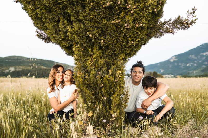 Portrait of a young family smiling and happy looking at the camera on the outside. Family having fun in the countryside royalty free stock photo