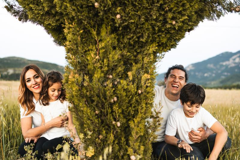 Portrait of a young family smiling and happy looking at the camera on the outside. Family having fun in the countryside royalty free stock image