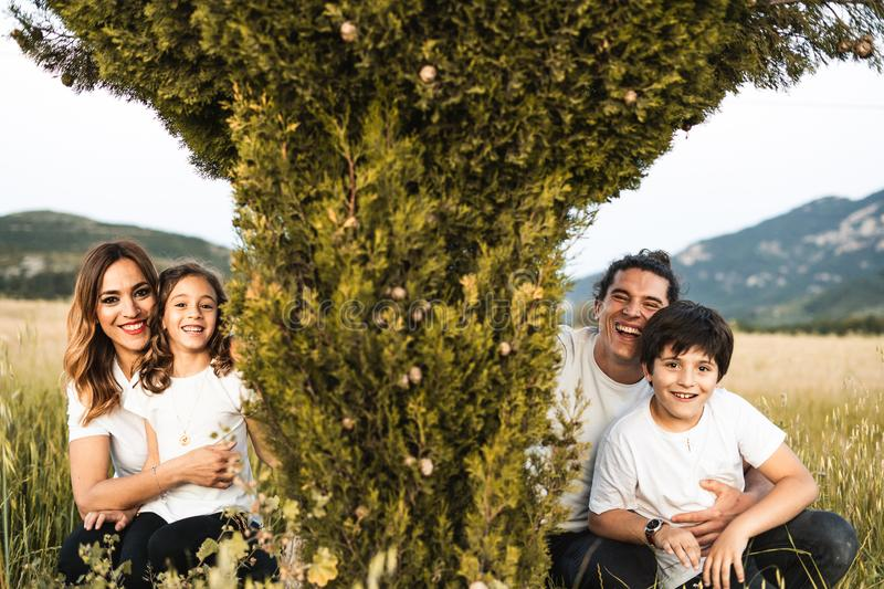 Portrait of a young family smiling and happy looking at the camera on the outside. Family having fun in the countryside stock photo