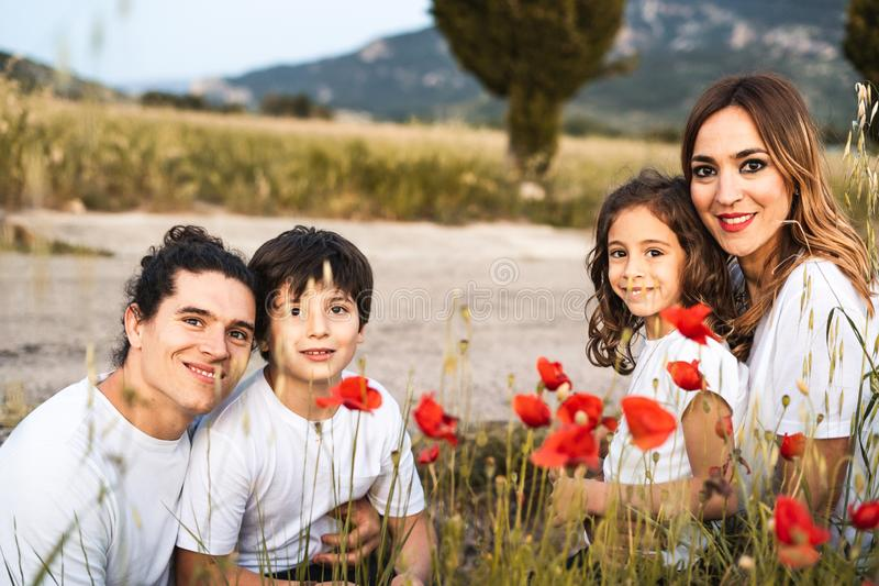 Portrait of a young family smiling and happy looking at the camera on the outside. Family having fun in the countryside royalty free stock images