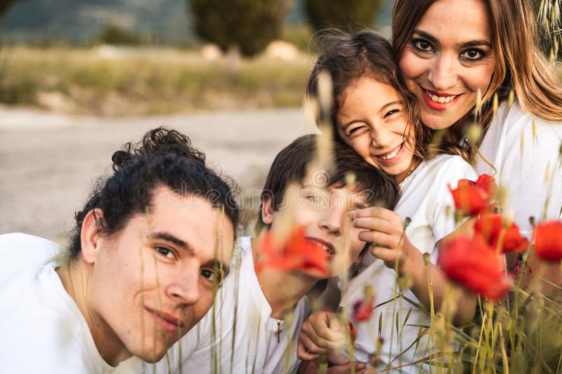 Portrait of a young family smiling and happy looking at the camera on the outside. Family having fun in the countryside stock photography